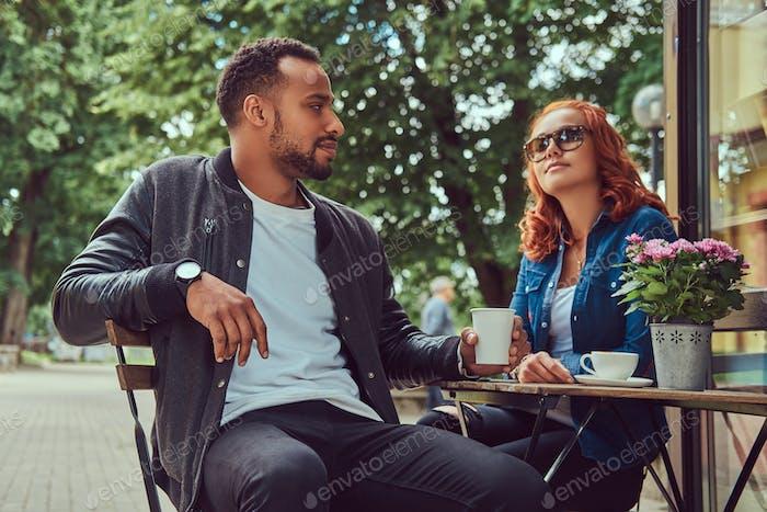 Ein Paar, das Kaffee trinkt, sitzt in der Nähe des Coffeeshops. Draußen auf einem Date.