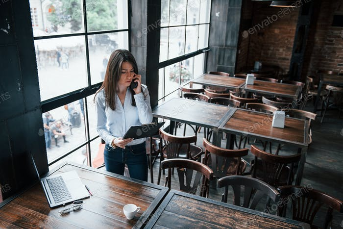 Businesswoman in official clothes is indoors in cafe at daytime