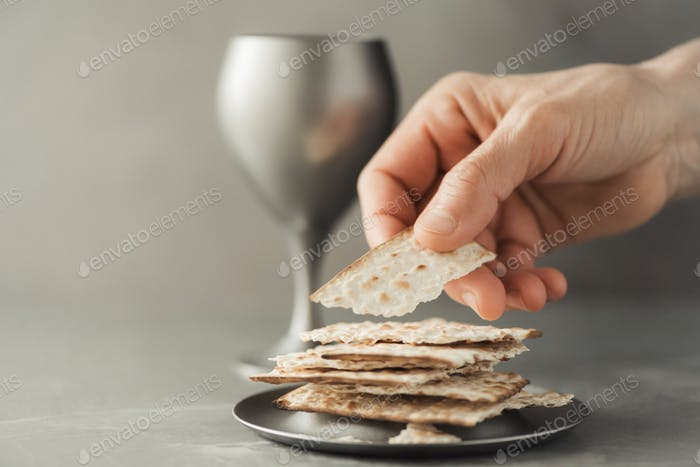 Hands with chalice and communion matzo bread, wooden cross on grey background. Christian communion
