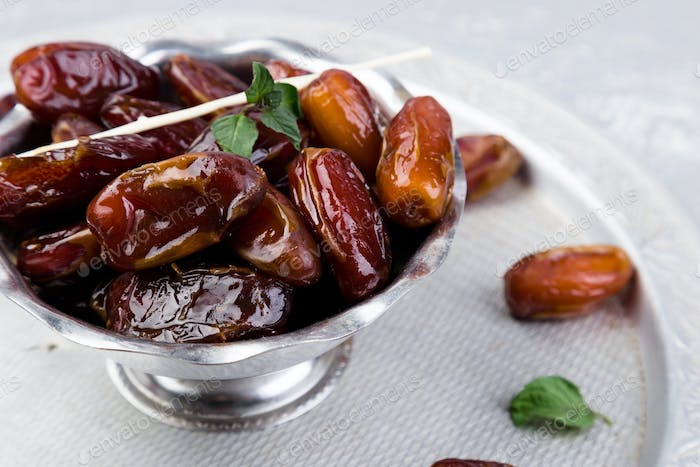 Dry fruit dates on silver tray. Copy space.