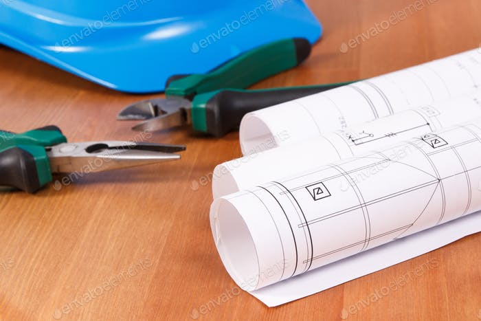 Rolls of electrical construction drawings, protective helmet and work tools for engineer jobs