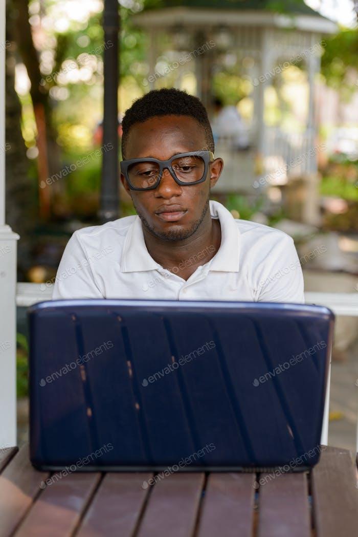 Junger afrikanischer Mann als Student mit Laptop im Park