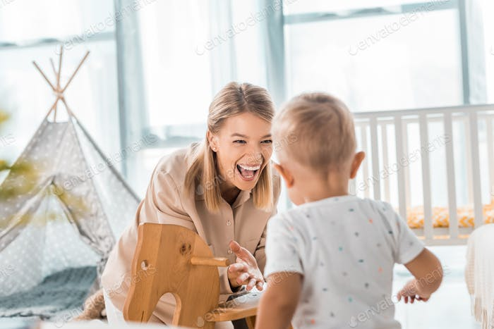 happy mother and toddler playing with toy wooden rocking horse chair in nursery room