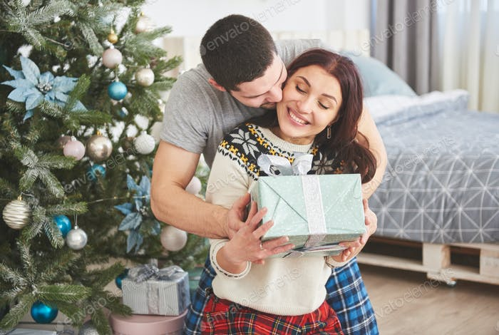 A man suddenly presented a present to his wife. The concept of family happiness and well-being