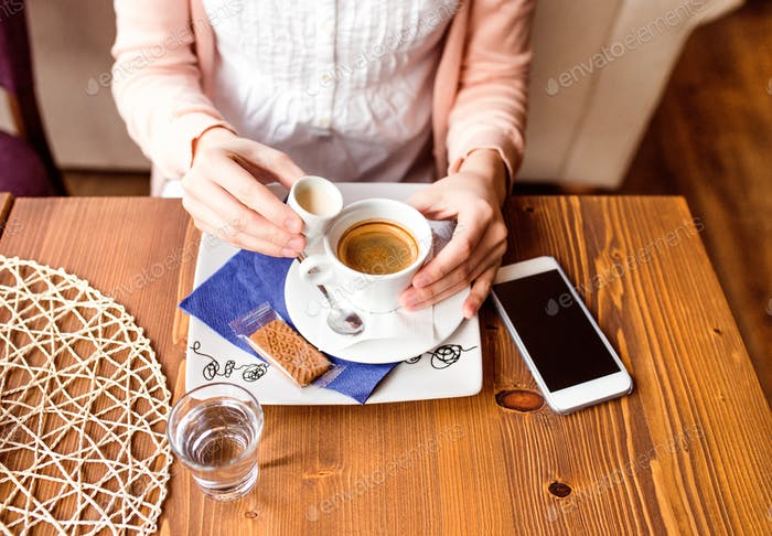 Unrecognizable woman in cafe drinking coffee, pouring cream in
