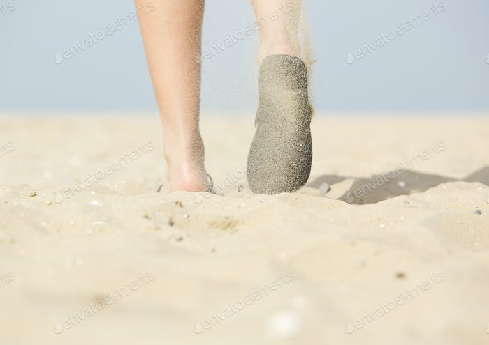 Woman walking with flip flops on beach