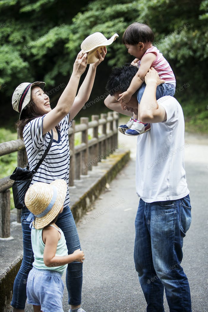 Japanese girl, smiling woman holding hat and man carrying toddler on his shoulders