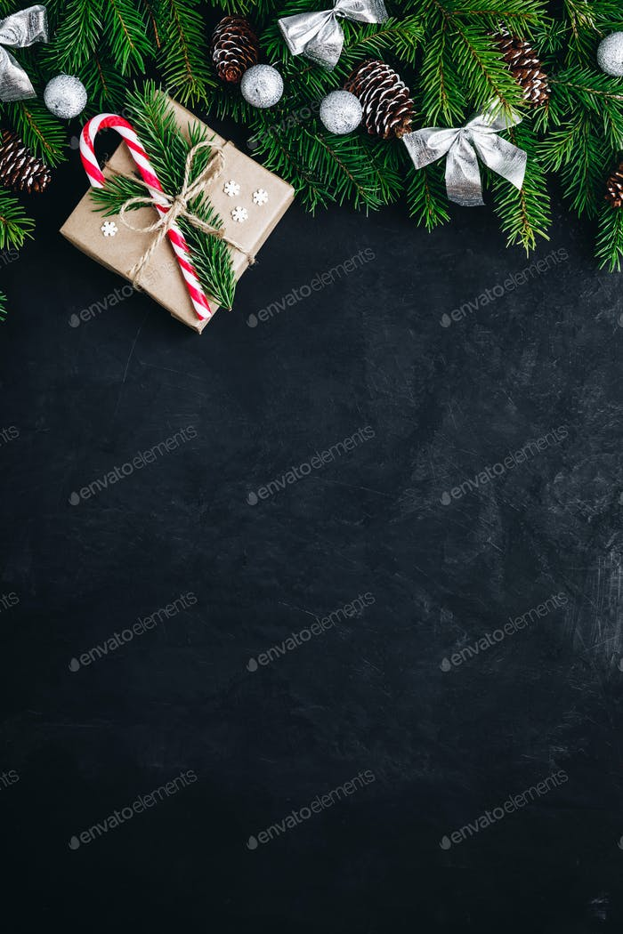 Christmas festive background with christmas tree branches, fir cones and gift box with candy cane