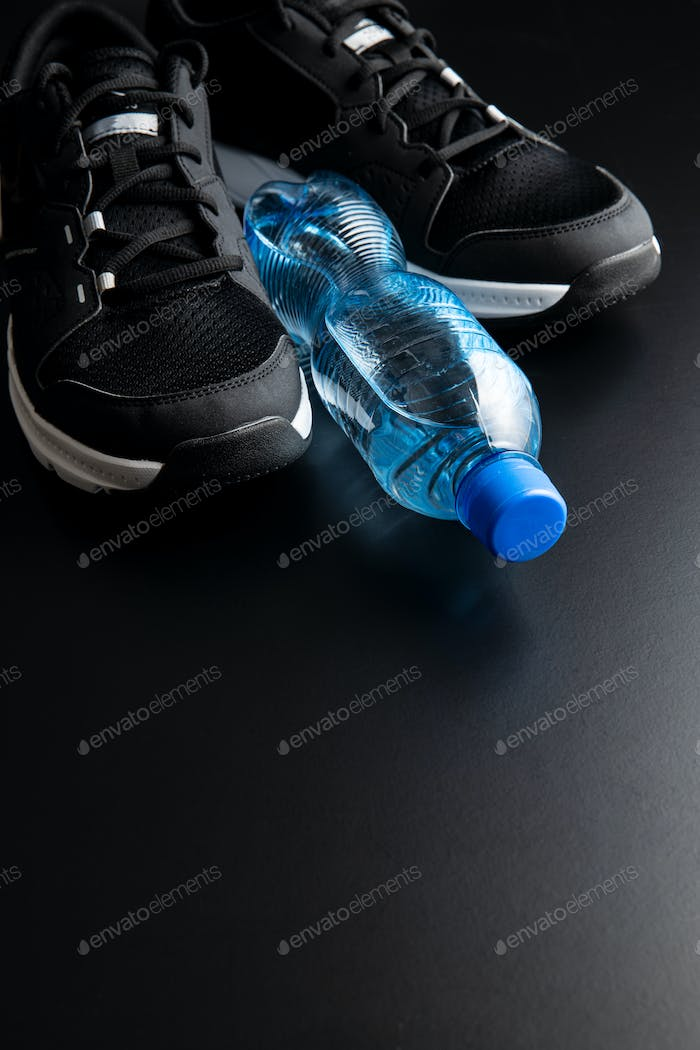 Black sport shoes and bottle of water