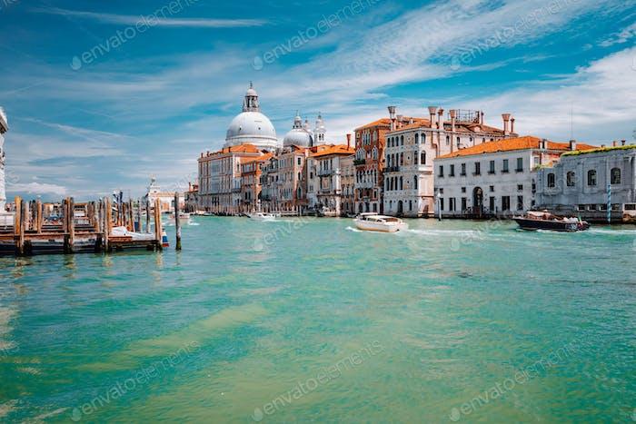 Grand Canal türkisfarbenes Wasser und Basilika Santa Maria della Salute am blauen Himmel, Venedig, Italien
