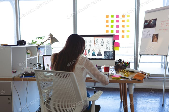 Rear view of young Caucasian female fashion designer working at desk in a modern office