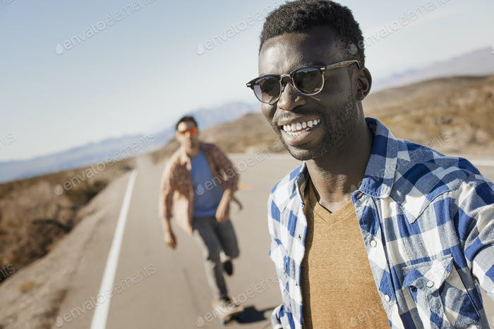 Two men on a tarmac road in open country.