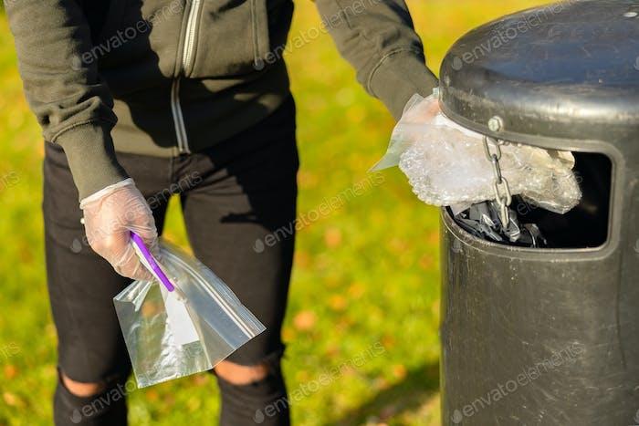 Volunteer putting plastic trash in garbage bin at park