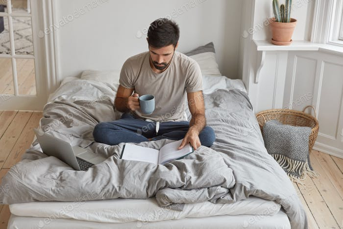 Image of young Caucasian man has morning coffee, sits crossed legs on bed, reads book, prepares for