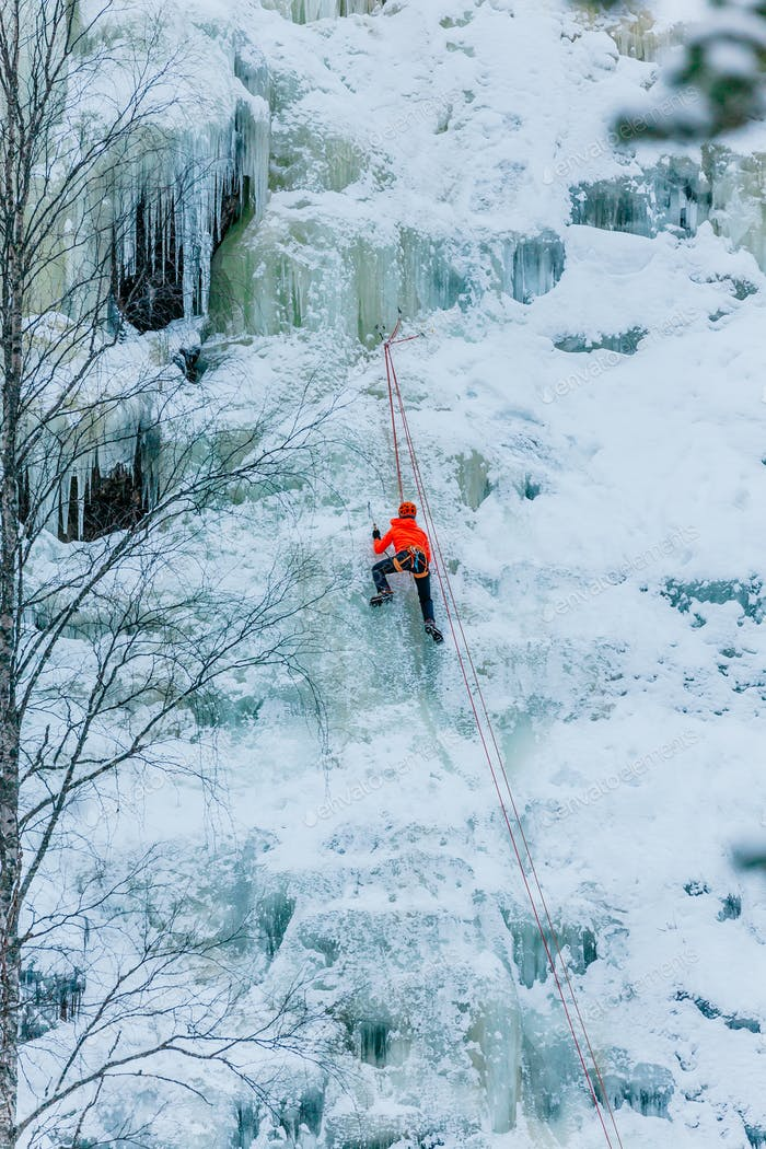 Athletic man in climbing a large blue wall of ice in Finland