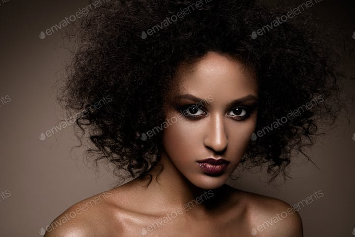 Fashion studio portrait of beautiful african american woman with perfect smooth glowing mulatto skin