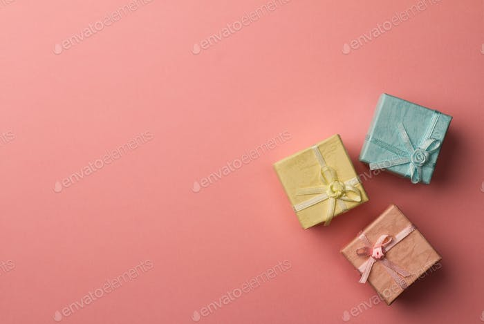Three small gift boxes with ribbons on pink background