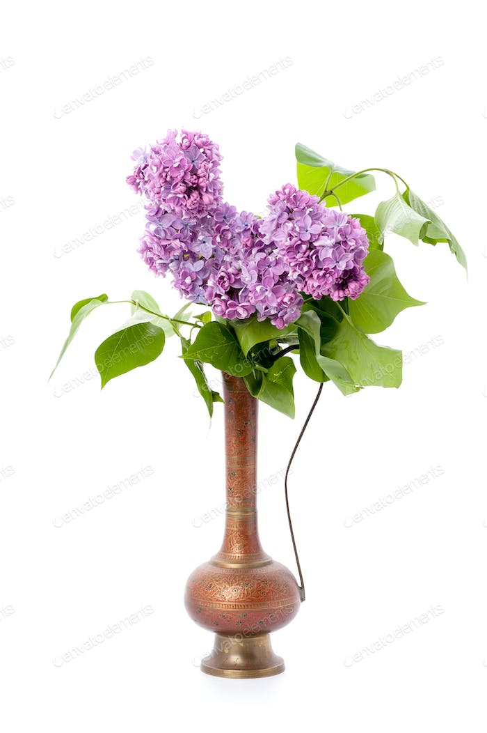 A bouquet of pink lilac in an oriental copper jar on a clean whi