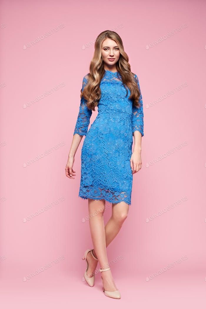 Blonde junge Frau in eleganten blauen Kleid