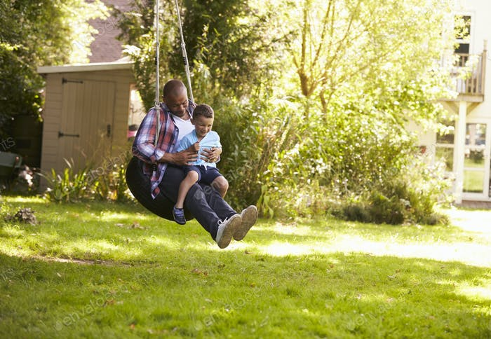 Father And Son Having Fun On Tire Swing In Garden