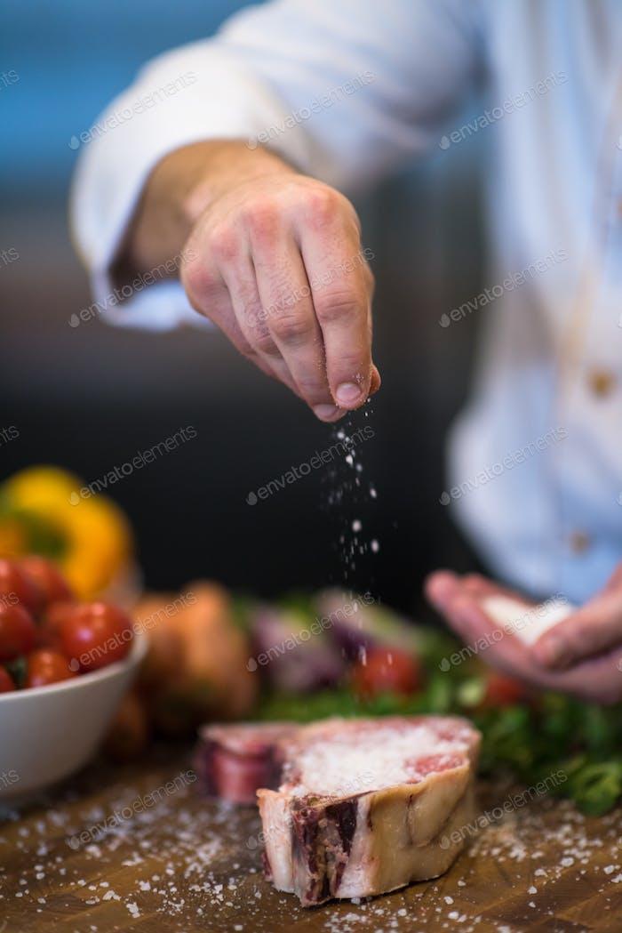 Chef putting salt on juicy slice of raw steak