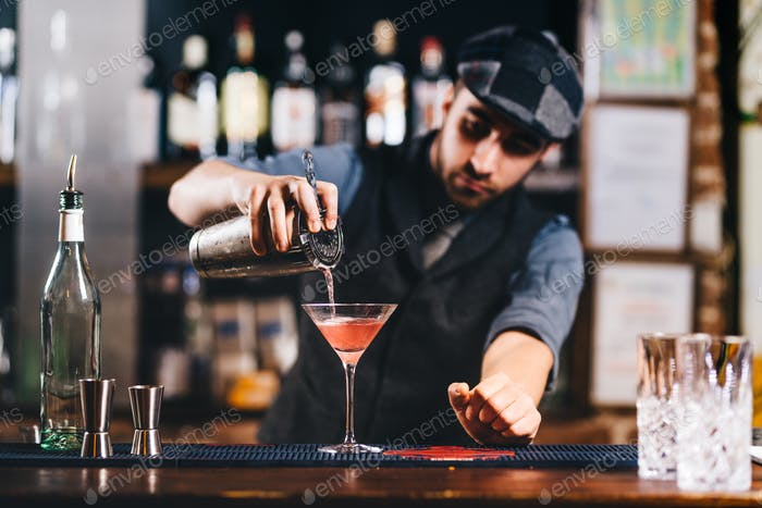 Portrait of vintage barman workin in bar. Pouring and preparing cocktails