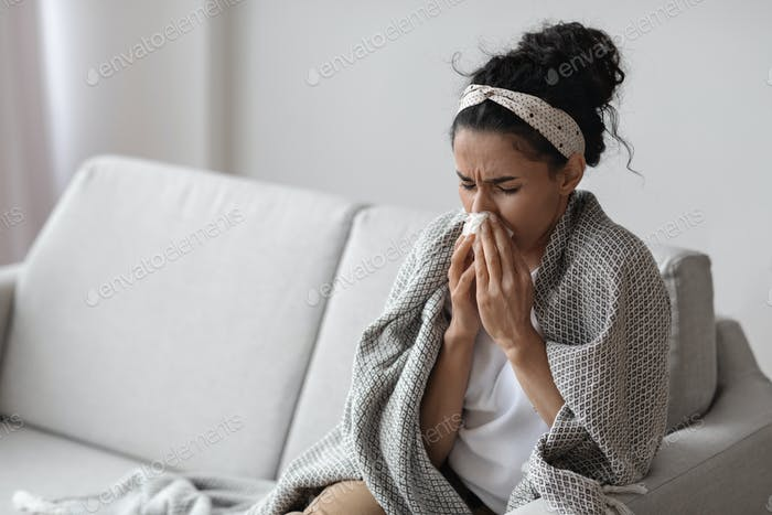 Sick young woman wrapped in blanket sneezing, home interior