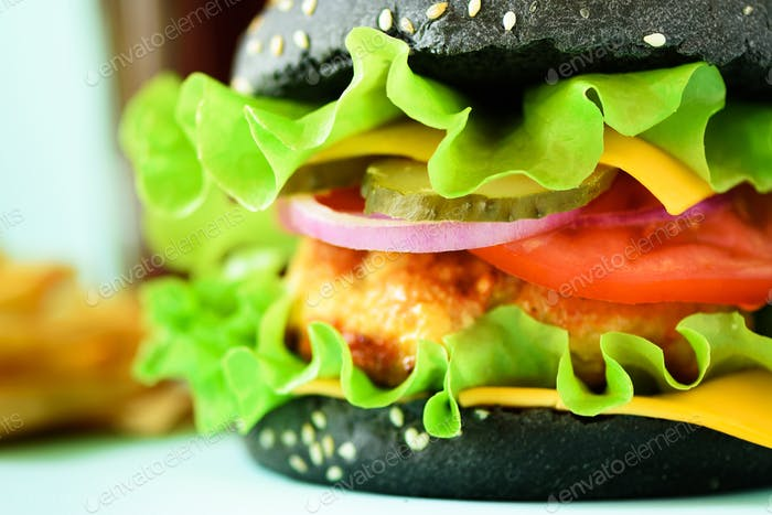 Macro view of tasty black burger with beef, cheese, lettuce, onion, tomatoes on blue background
