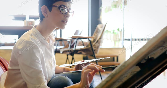 Женский художник живопись с палитрой и кистью