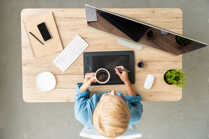 overhead view of female freelancer drinking coffee working on graphic tablet at table with