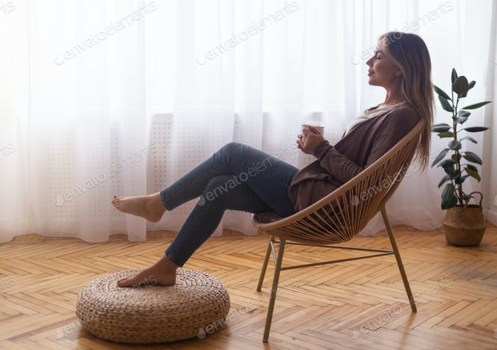 Calm girl drinking coffee, relaxing near window at home
