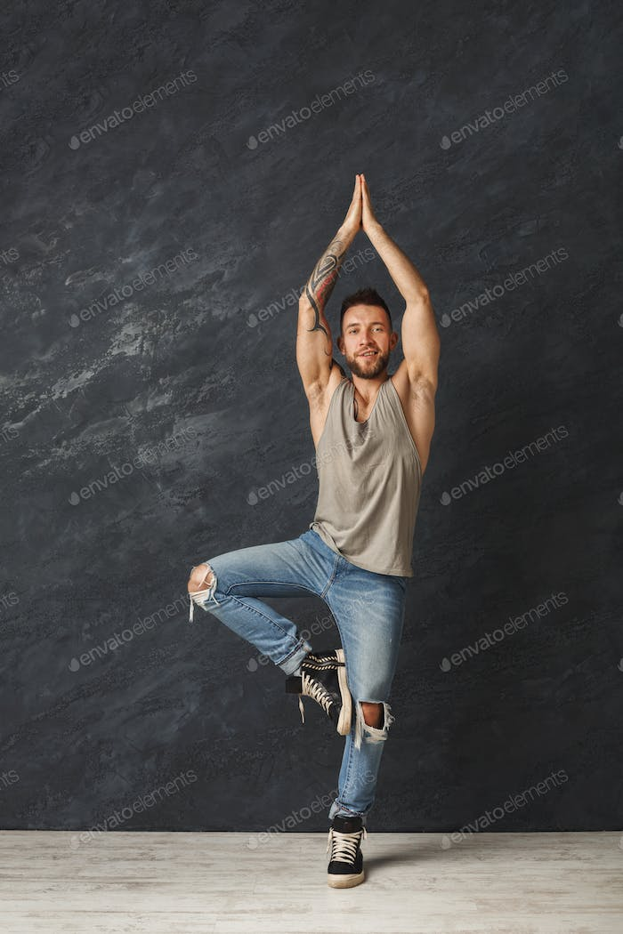 Happy handsome man making a yoga pose in studio