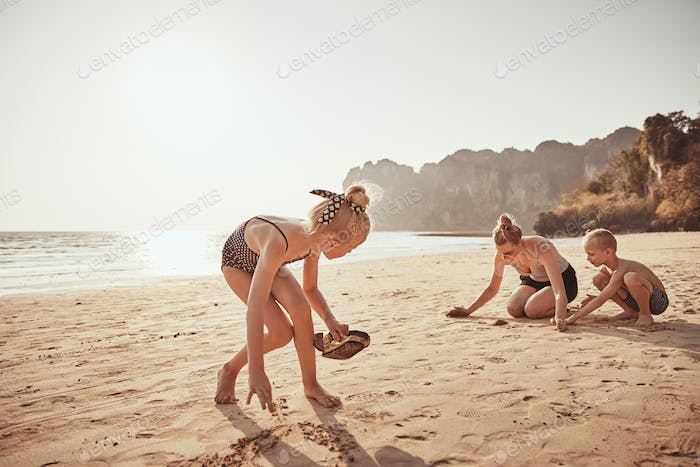 Cute little girl playing at the beach with her family