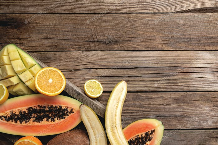 Fresh tropical fruits in a wooden box on a wooden background