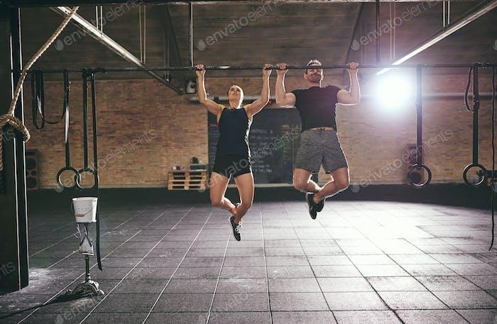Front shot of two sportsmen doing pull-ups