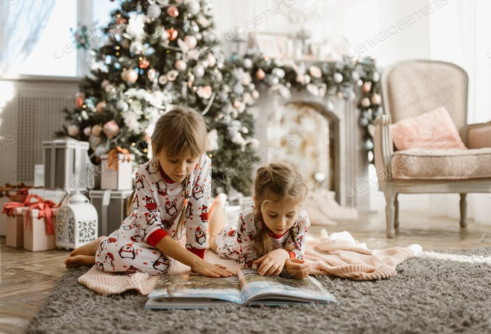 Two little sisters sit on the carpet and read book near the New Year's tree with gifts in the