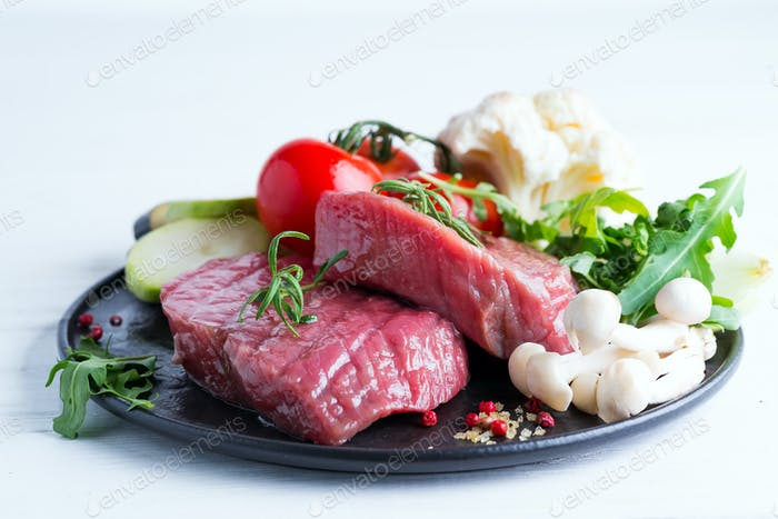 Raw beef steak on the bone with fresh vegetables in a pan on a white background, top view