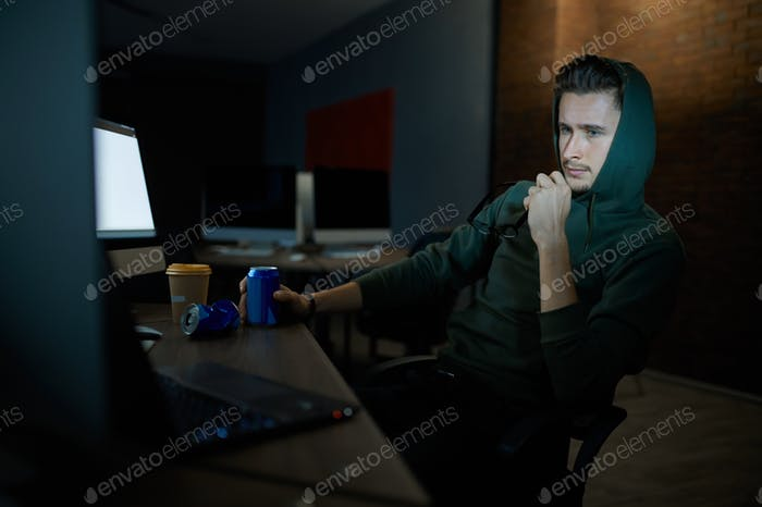 Male internet hacker in hood leisures at monitors