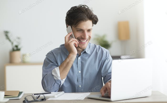 Happy Entrepreneur Talking On Cellphone Sitting At Laptop In Office
