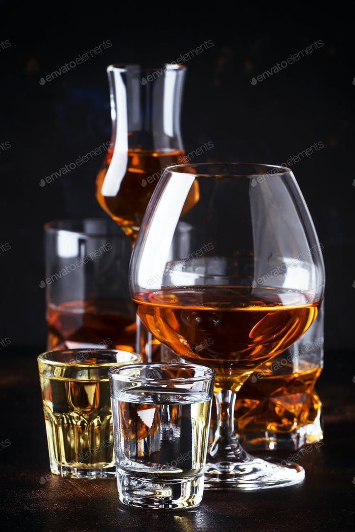 strong alcoholic drinks in glasses and shot glass in assortment: vodka, rum, cognac, tequila