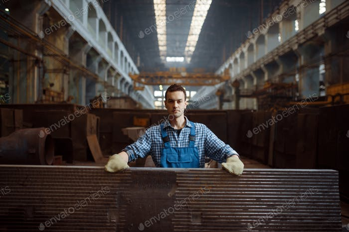 Male worker at stack of metal workpieces