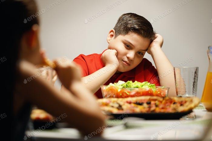Madre dando ensalada en lugar de pizza para hijo con sobrepeso