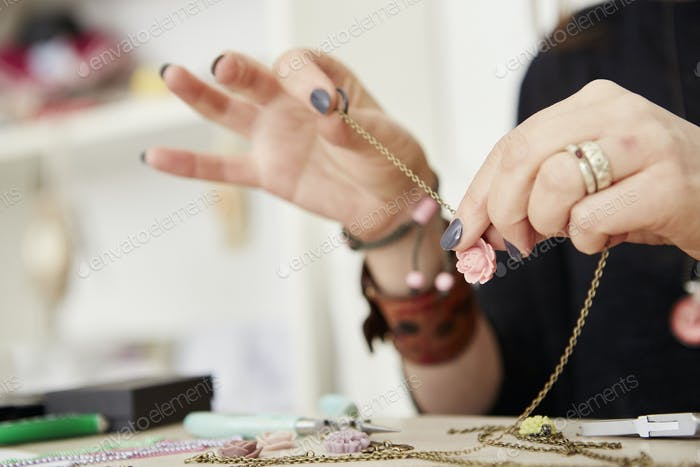 A woman seated at a workbench holding a gold chain with a small floral pendant, making jewellery.