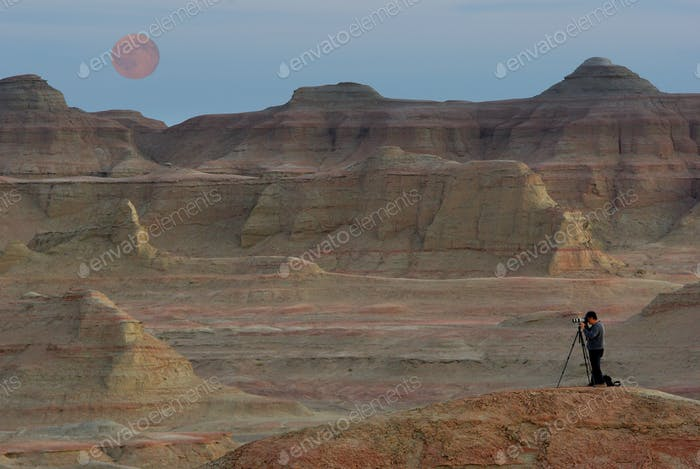 Photographer take photo on the fantastic mountain background with full moon, extreme,