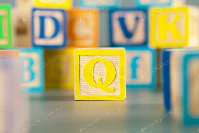 Fotografía del colorido bloque de madera letra Q