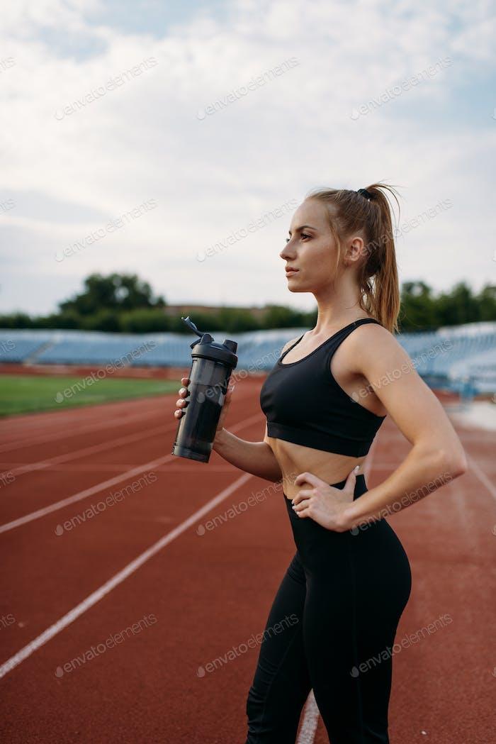 Female runner drinks water, training on stadium