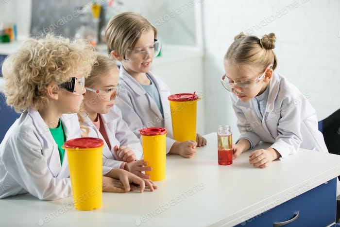 Дети в защитных очках делают эксперимент в лаборатории