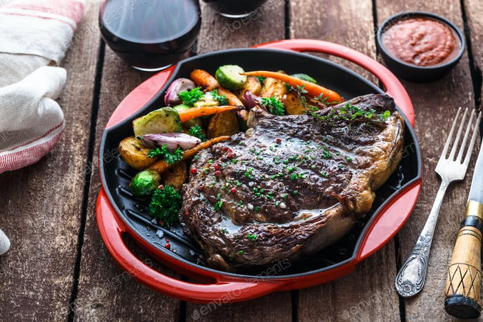 Juicy beef steak close view on iron cast pan with root vegetables