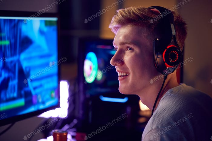 Teenage Boy Wearing Headset Gaming At Home Using Dual Computer Screens
