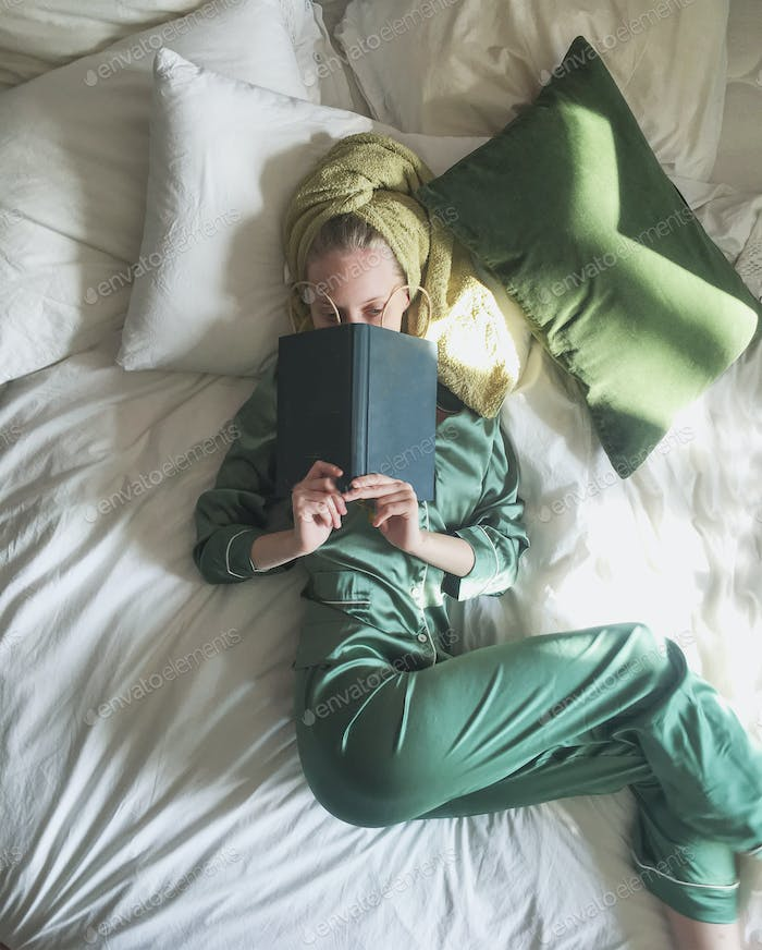 Young blonde female in silky pyjamas with book in bed